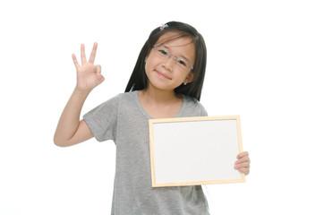 Little Asian girl holding empty whiteboard