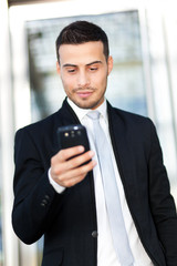 Portrait of a young businessman texting on the phone