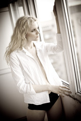 Attractive sexy blonde with white shirt looking on the window