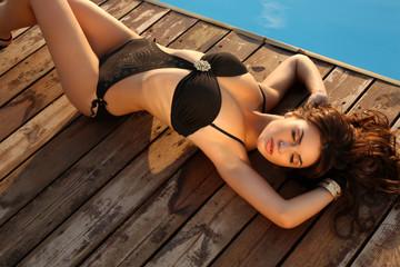 sexy girl with dark hair in bikini relaxing on beach