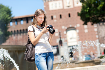 Smiling female tourist taking photos