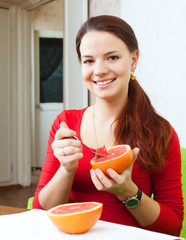 beautiful woman in red eats grapefruit