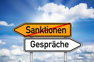 Wegweiser mit Sanktionen und Gespräche