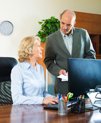 office scene with two mature and serious workers