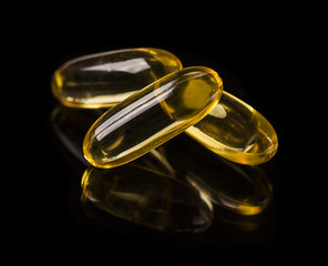 Cod liver oil omega 3 gel capsules on the dark glass