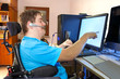 Man with infantile cerebral palsy using a computer. - 69639431