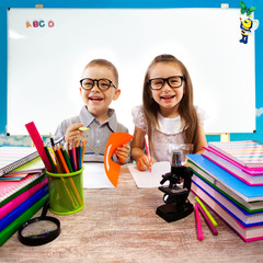Two kids at the table  in classroom on lesson