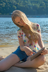 Girl on the beach with the tablet