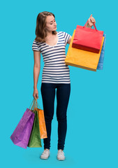 Young happy girl with shopping bags on a blue background
