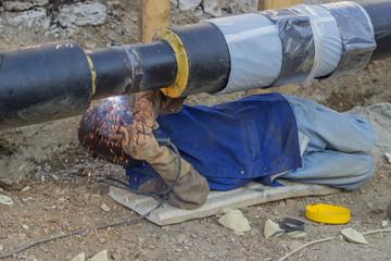 Welder welding underground steel pipe lying on ground 4