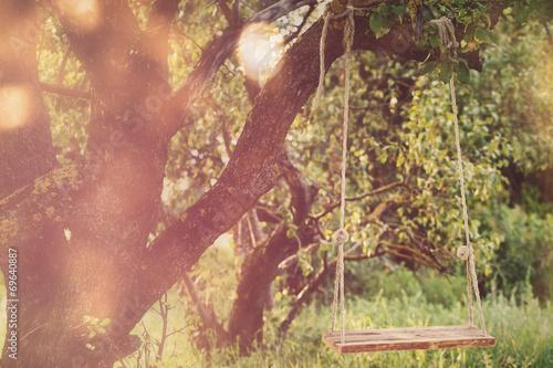 Leinwanddruck Bild Empty swing in the park