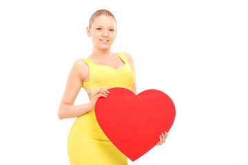 Attractive woman holding a red heart