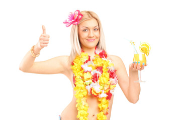 Woman in hawaiian costume drinking cocktail and giving thumb up