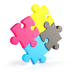 Four assembling colorful puzzle pieces in cmyk
