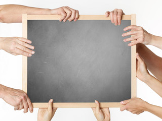 Many hands holding a blank blackboard
