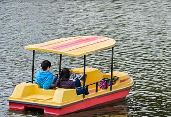 Река, озеро. Молодая пара катается на водном велосипеде