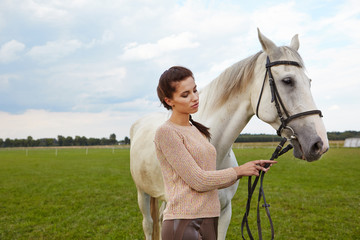 An attractive young woman with a horse