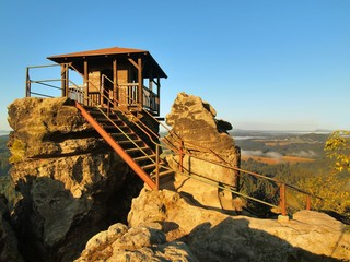 Wooden tourist cabin on main peak of rock, steel wooden lader