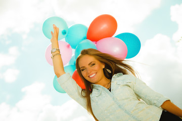 Happy girl with colorful balloons outdoors