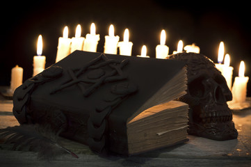 Magic book with candles and skull in the darkness
