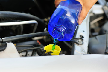 hand adding auto glass cleaner for car
