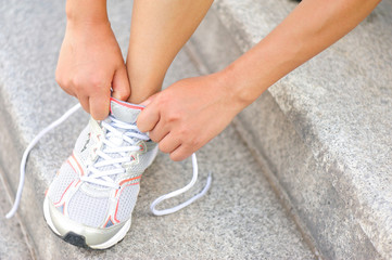woman runner tying shoelace on stone stairs