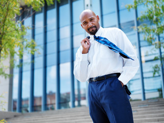 confident african businessman with tie blowing in the wind