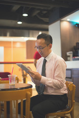 hong kong business man having coffee at cafe with tablet , vinta