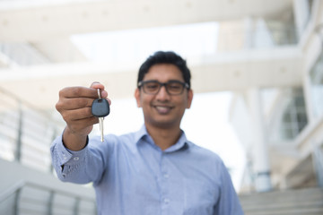 Young Asian Indian estate agent or salesman holding a key, India