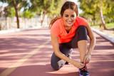 Happy runner tying her shoes