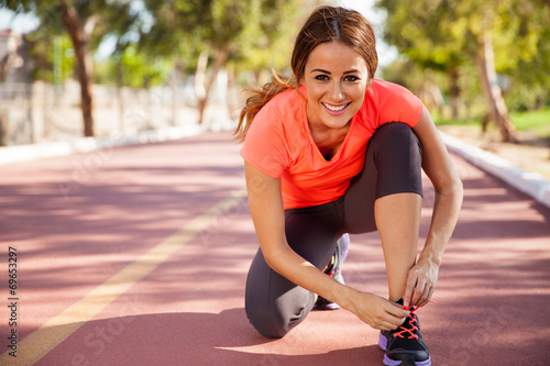 Happy runner tying her shoes - 69653297