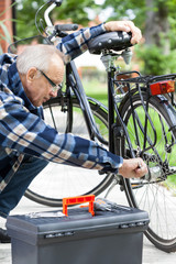Older man repairing a bicycle