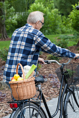 Man on a bicycle is carrying a vegetable basket