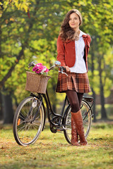 Fashionable woman posing with her bicycle in park