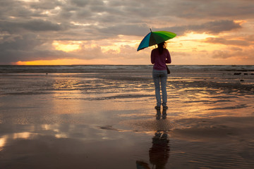Young woman with colorful umbrella, standing on the beach