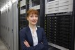 Pretty technician smiling at camera beside server tower - 69655229