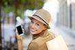 Leinwanddruck Bild - Smiling shopping girl using smartphone in town