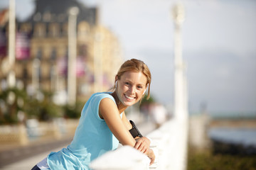 Cheerful jogger relaxing after running in town