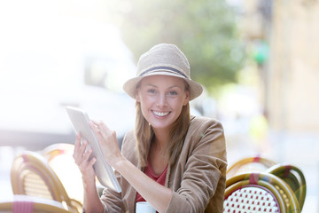 Trendy girl at coffee shop websurfing on internet with tablet