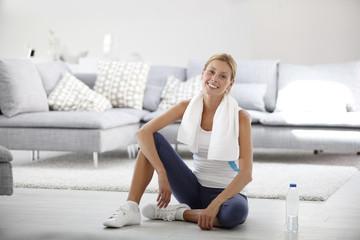 Young woman at home stretching out after exercising