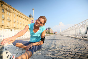 Woman in town stretching out after running