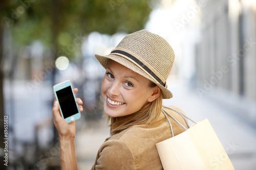 Leinwanddruck Bild Smiling shopping girl using smartphone in town