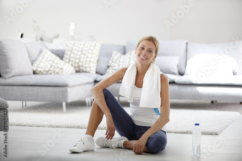 canvas print picture Young woman at home stretching out after exercising