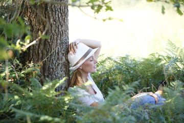 Young woman with hat relaxing in forest