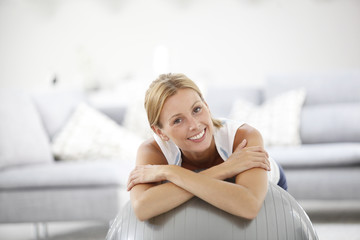 Smiling woman relaxing on gym ball at home