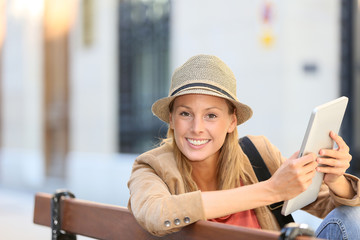 Smiling trendy girl using tablet in town