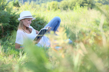 Relaxed woman reading book in countryside
