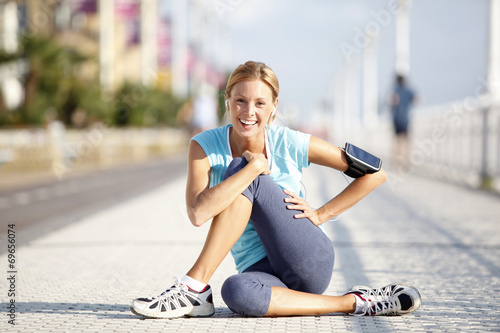 canvas print picture Cheerful jogger stretching after exercising in the street