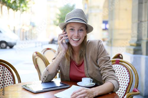 Cheerful modern girl in coffee shop talking on phone - 69656215