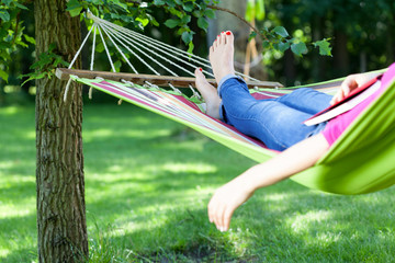 Lady lying with book on hammock